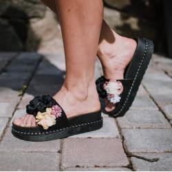 Melnas ziedu čības uz platformas